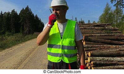 Forest officer talk on walkie-talkie near the stack of logs