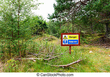 """Forest sign reading """"Danger! Keep Out!"""" warning tourist of a..."""