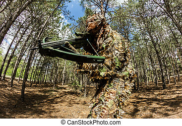 Forest sniper hunter in camouflage posing with crossbow.