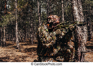 Forest sniper hunter in camouflage sitting with crossbow.