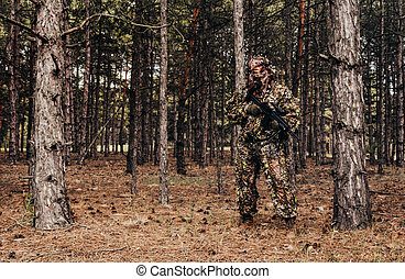 Forest sniper hunter in camouflage standing with crossbow.