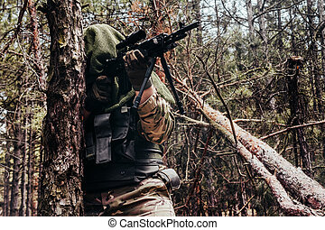 Forest sniper in camouflage aiming with rifle.