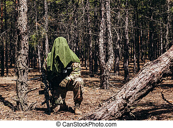 Forest sniper in camouflage sitting with rifle.