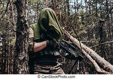 Forest sniper in camouflage standing with rifle.