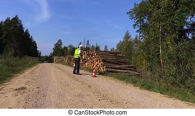 Forest worker put road cones on rural road near log pile