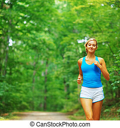 Forested Road Runner - Woman runner exercising, from a...