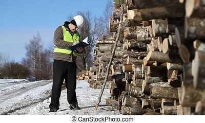 Forester with cell phone and folder near at the log pile