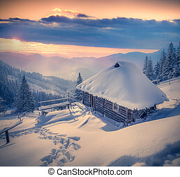 Forester's hut covered with snow in the mountains at sunrise.
