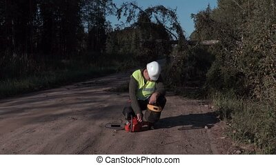 Forestry worker inspecting the chainsaw on the road near...