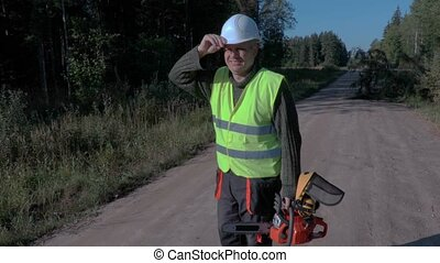 Forestry worker on the road with chainsaw near broken and...