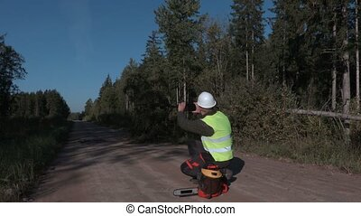 Forestry worker take picturese near broken and fallen spruce...