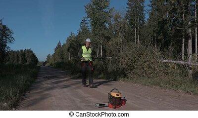 Forestry worker talking on the phone near fallen spruce