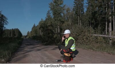 Forestry worker talking on the phone near chainsaw on forest...