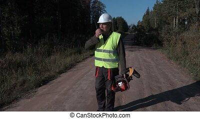 Forestry worker using walkie talkie on the road near broken...