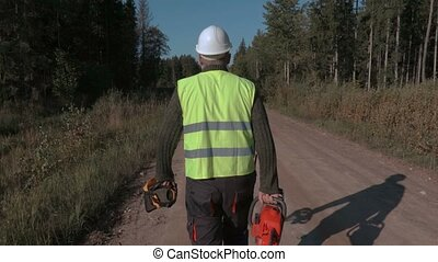 Forestry worker walking on the road with chainsaw