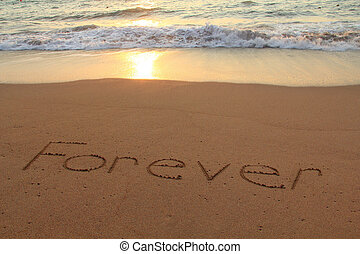 Forever written in the sand on a beach at sunset.