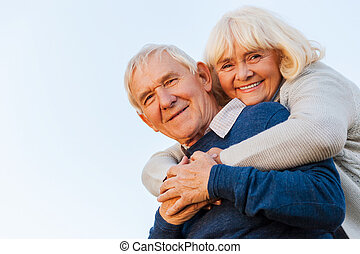 Forever young. Low angle view of happy senior couple bonding to each other and smiling with blue sky as background