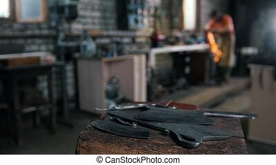 Forged items on the background of a blurred blacksmith -...