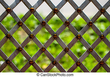 forged mesh with green grass on background