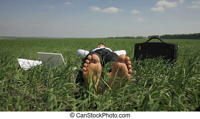 Business man lying on the grass and relaxing forgetting about his usual obligations