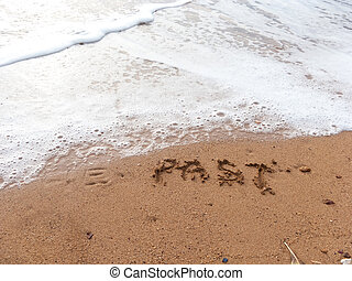 Forget the past - Word Forget in handwriting on sandy beach