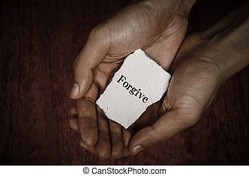 Forgive stone block in hands with dark background.