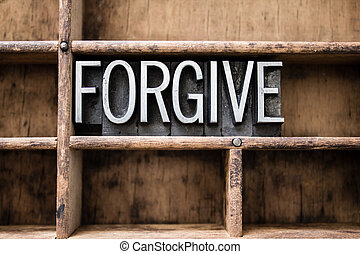 """The word """"FORGIVE"""" written in vintage metal letterpress type in a wooden drawer with dividers."""