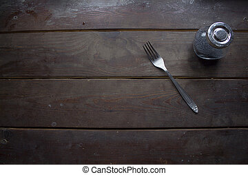Fork and a jar with, brown wooden surface