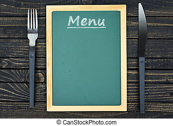 Fork and knife with menu on table
