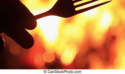 fork in hand against a background of fire
