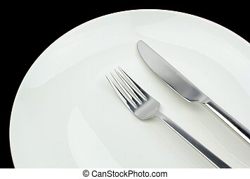 Fork, knife and plate on a black background.