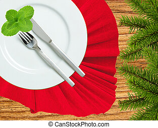Fork, knife and white plate on a red cloth and christmas tree on wooden table