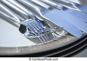 place setting of four plates forks knives on table