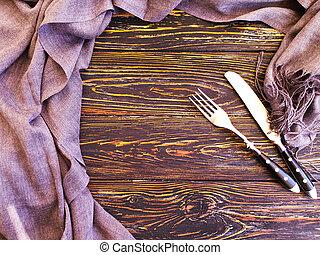 fork, knife towel on old wooden background
