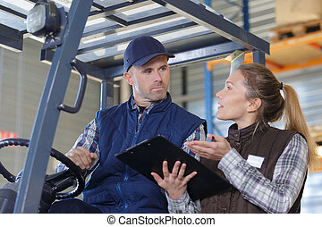 fork lift truck driver discussing checklist with manager in warehouse