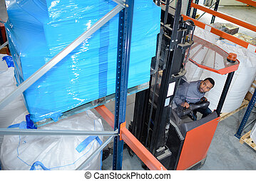fork lift truck driver working in warehouse