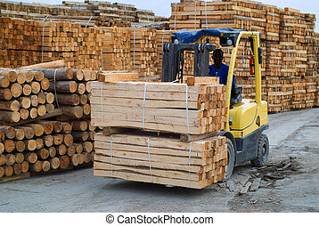 Fork lift truck in wood factory - Yellow folk lift truck in...