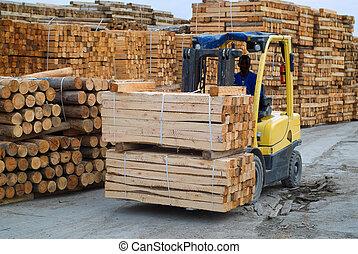 Fork lift truck in wood factory - Yellow folk lift truck in ...