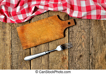 Fork next to wooden cutting board and a red checkered tablecloth top frame on wooden table background