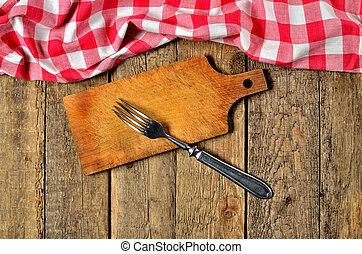Fork on wooden cutting board and a red checkered tablecloth top frame on wooden table background