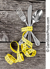 Fork, spoon, knife and measuring tape on a thin wooden...
