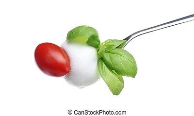fork tomato basil mozzarella topped with spilled oil...