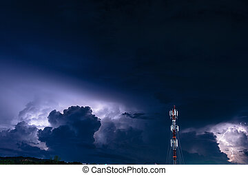 Forked lightning over the cell phone antenna tower at night