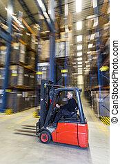 A man driving a forklift trough a warehouse