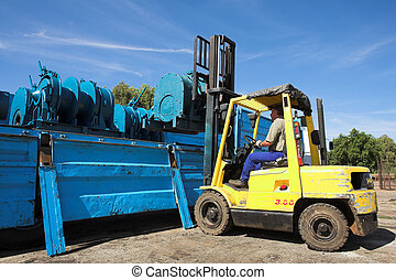 forklift #1 - Yellow Forklift placing cargo on Flatbed truck...
