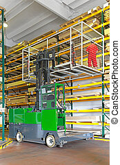 Side loaded forklift with basket in wood warehouse