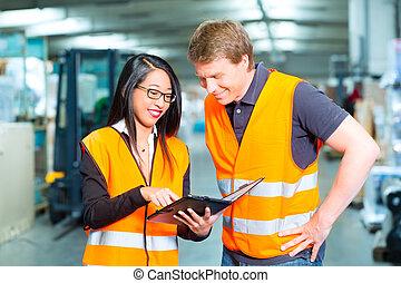 Forklift driver and supervisor at warehouse