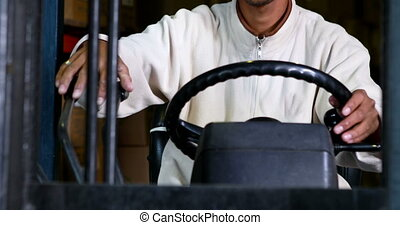 Forklift driver operating the machine in a large warehouse