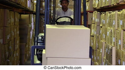 Forklift driver picking up palette of boxes in a large...