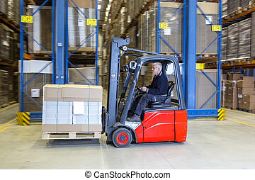Forklift driving alongside a storage rack. - Man is driving...